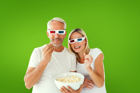 Happy couple wearing 3d glasses eating popcorn against green vignette photo
