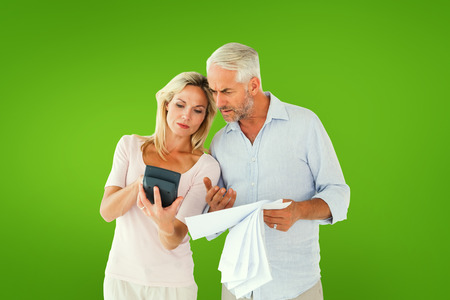 figuring: Anxious couple working out their bills against green vignette