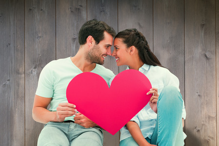 Cute couple sitting holding red heart against wooden planks