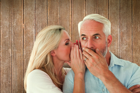 secret: Woman whispering a secret to husband against wooden planks