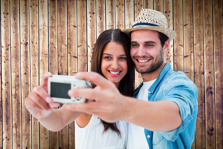 Happy hipster couple taking a selfie against wooden planks photo