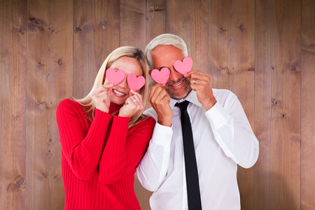 ttractive: Silly couple holding hearts over their eyes against wooden planks Stock Photo