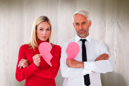 Couple not talking holding two halves of broken heart against wooden planks photo
