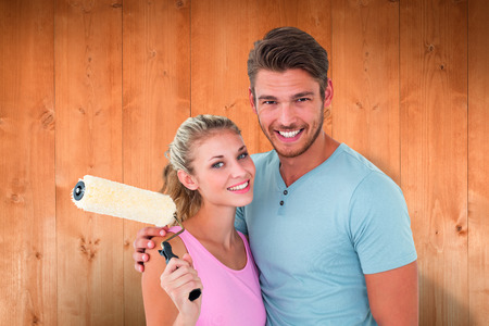 Young couple hugging and holding paint roller against wooden planks photo