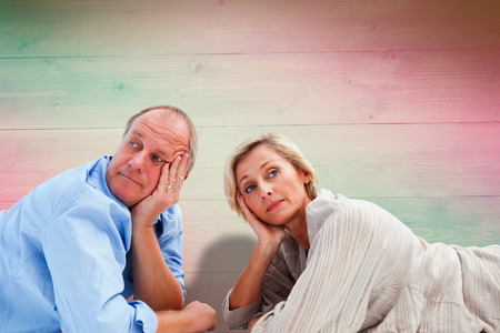 exasperated: Mature couple lying and thinking against pink and green planks