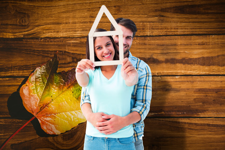 Happy young couple with house shape against wooden table with autumn leaves