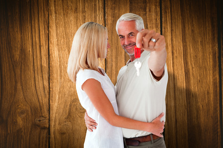 Happy couple showing their new house key against wooden table photo