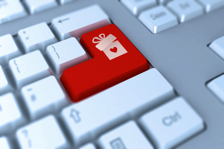 keyboard keys: gift with heart against red enter key on keyboard Stock Photo