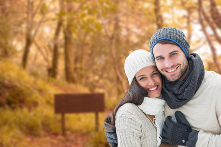 Young winter couple against tranquil autumn scene in forest photo