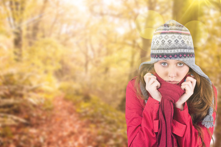 Cold redhead wearing coat and hat against tranquil autumn scene in forest photo
