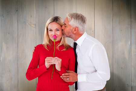 Handsome man giving his wife a kiss on cheek against wooden planks photo