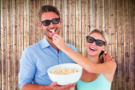 Happy young couple wearing 3d glasses eating popcorn against wooden planks photo