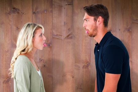 strife: Childish couple having an argument against wooden planks Stock Photo