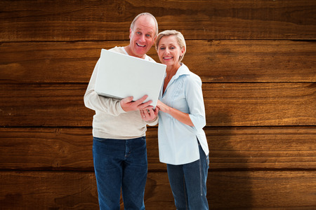 Mature couple smiling at camera with laptop against overhead of wooden planks photo