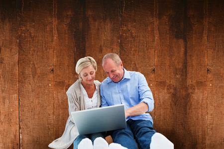 Happy mature couple using laptop against weathered oak floor boards background photo
