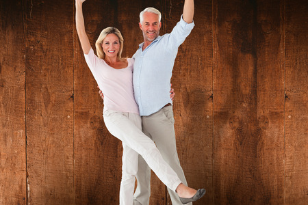 chinos: Smiling couple cheering at the camera against weathered oak floor boards background Stock Photo