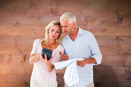 figuring: Anxious couple working out their bills against bleached wooden planks background