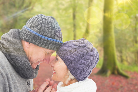 Mature winter couple against peaceful autumn scene in forest photo