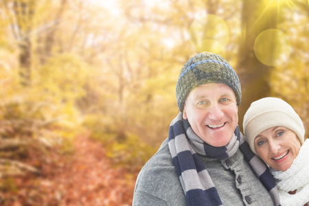 Mature winter couple against tranquil autumn scene in forest photo