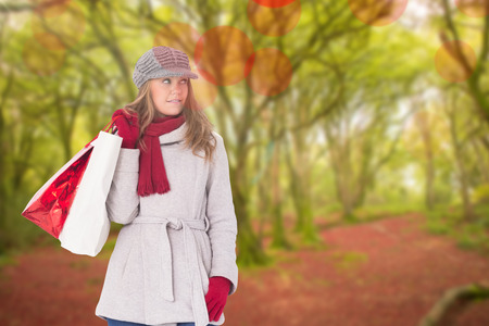 Happy blonde in winter clothes with bags against peaceful autumn scene in forest photo