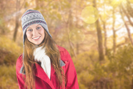 Pretty redhead in warm clothing against tranquil autumn scene in forest photo
