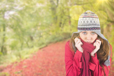 Cold redhead wearing coat and hat against peaceful autumn scene in forest photo