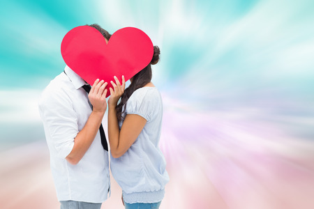 girly: Couple covering their kiss with a heart against digitally generated pink and blue girly design