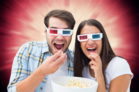 Attractive young couple watching a 3d movie against valentines heart design photo