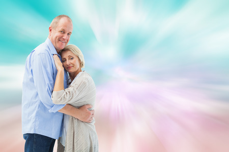 girly: Happy mature couple hugging and smiling against digitally generated pink and blue girly design