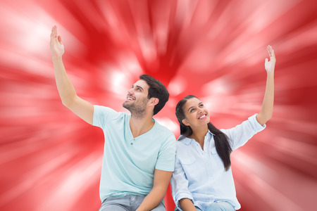 arms raised: Cute couple sitting with arms raised against digitally generated twinkling light design Stock Photo