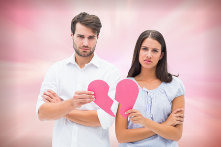 exasperated: Upset couple holding two halves of broken heart against digitally generated pink girly design