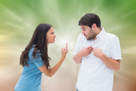 accusing: Angry brunette shouting at boyfriend against digitally generated dandelion seeds on green background