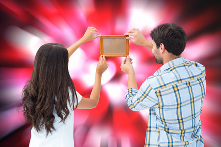 putting up: Happy young couple putting up picture frame against valentines heart pattern