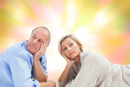 exasperated: Mature couple lying and thinking against girly pink and yellow pattern