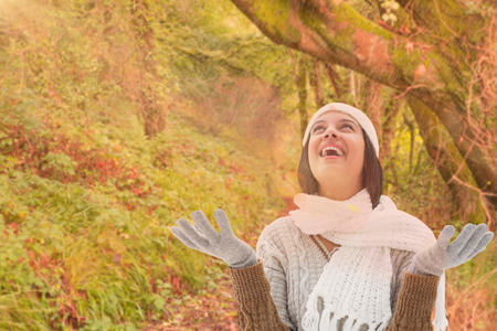 warm clothing: Brunette in warm clothing against peaceful autumn scene in forest Stock Photo