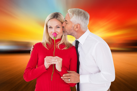 Handsome man giving his wife a kiss on cheek against countryside scene photo