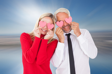 ttractive: Silly couple holding hearts over their eyes against room with large window looking on city