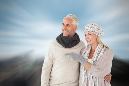rock wool: Happy couple in winter fashion looking against large rock overlooking big city
