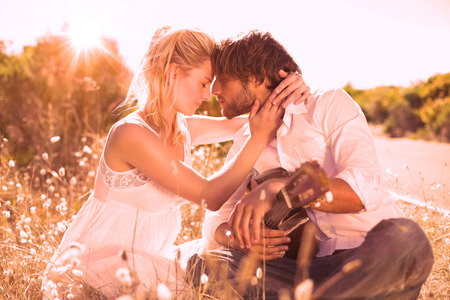 serenading: Handsome man serenading his girlfriend with guitar on a sunny day Stock Photo