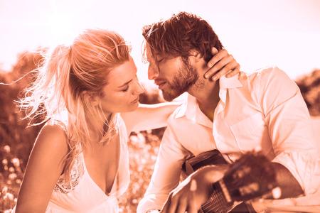 serenading: Handsome man serenading his girlfriend with guitar in sepia tones Stock Photo