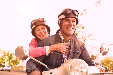 mature couple: Happy senior couple riding a moped on a sunny day Stock Photo