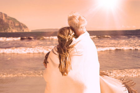 hair wrapped up: Couple wrapped up in blanket on the beach looking out to sea on a sunny day