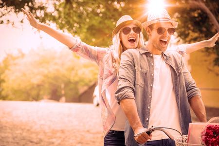 Şehirde güneşli bir günde bir bisiklete binmek için gidiş Hip genç çift