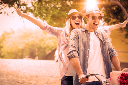 Hippe jonge paar gaan voor een fietstocht op een zonnige dag in de stad