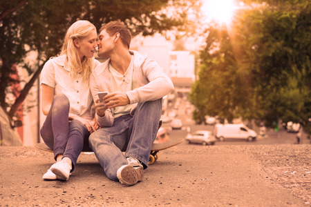 mid adult couple: Cute young couple sitting on skateboard kissing on a sunny day in the city