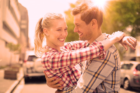 man woman hugging: Couple in check shirts and denim hugging each other on a sunny day in the city