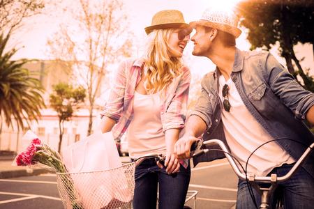 parejas: Pareja joven de la cadera en un paseo en bicicleta en un d�a soleado en la ciudad