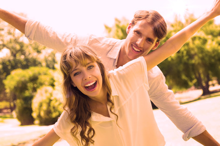 spreading arms: Attractive couple smiling at camera and spreading arms in the park on a sunny day Stock Photo