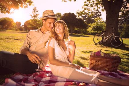 Casal bonito bebendo vinho branco em um piquenique, sorrindo um para o outro em um dia ensolarado