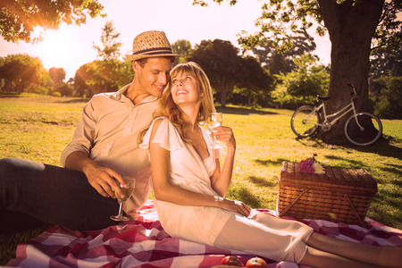 romantico: Linda pareja bebiendo vino blanco en un picnic sonriente uno al otro en un d�a soleado